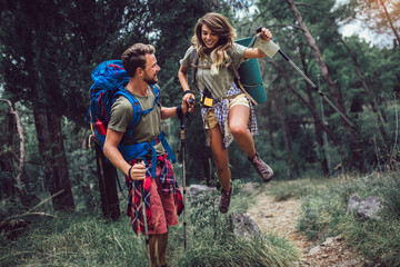 Backpackers couple hiking during fall with sticks