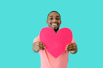 Portrait of an smiling young man holding pink heart in front of him with big smile, valentineÕs day love, give your heart concept