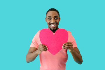 Portrait of an smiling young man holding pink heart in front of him with big smile, valentines' day love, give your heart concept