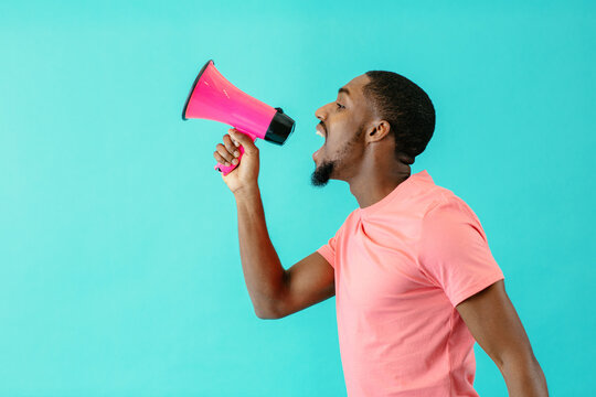Portrait of a young man shouting through megaphone with mouth open