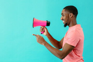 Portrait of a smiling young man with megaphone pointing and looking at copy space