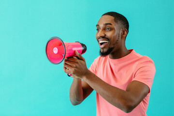 Portrait of a positive young man speaking through megaphone with mouth open
