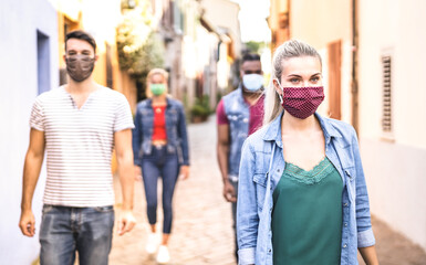 Multiracial friends walking with face mask after lockdown reopening - New normal friendship concept...