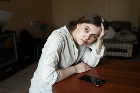 the victim of domestic violence and abuse, a girl sitting at a table, looking at the window holding her head in her hand, a man sleeping in the background