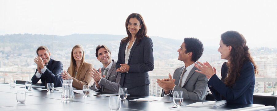 Coworkers clapping for businesswoman in conference room
