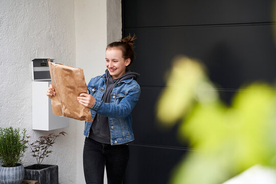 Girl standing in front of house, happy to receive a parcel