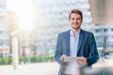 Smiling young businessman using tablet in the city