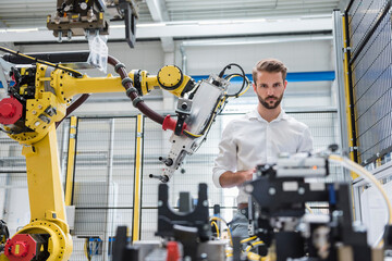 Confident male robotics expert looking at machinery in automated industry