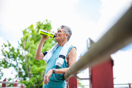 Low angle view of thirsty senior man drinking water from bottle while leaning on railing at park