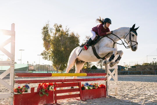 Teenage girl riding white horse while training for obstacle course on ranch