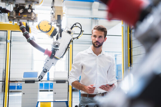 Confident engineer looking at robotic arm while standing with digital tablet in factory