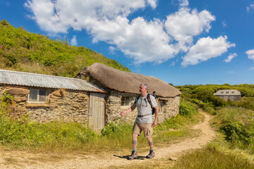 A hiker with a backpack on the Cornwall Coastal Path in sunshine in a rural setting. It is a sunny and warm day with a blue sky and nice clouds. There are many bushes, plants and flowers.