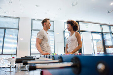 Young man amnd woman talking in office with a football table