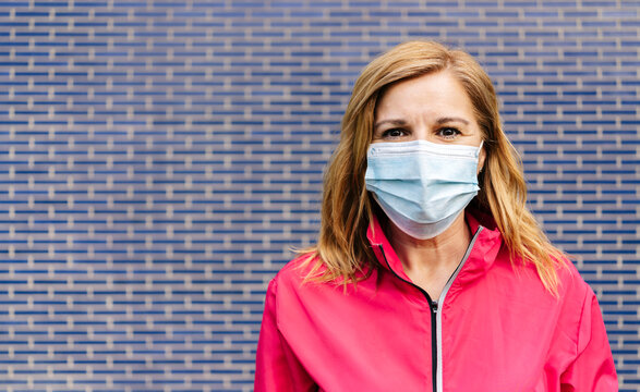 Woman with surgical mask in front of blue wall