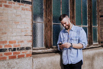 Smiling young man looking at cell phone outdoors Wall mural
