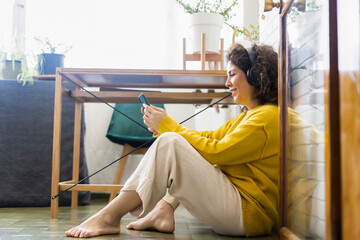 Smiling woman sitting on the floor at home wearing headphones and using smartphone