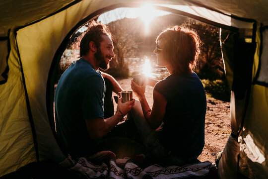 Happy couple camping at lakeside