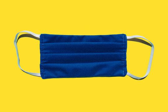 Studio shot of blue protective face mask against yellow background?