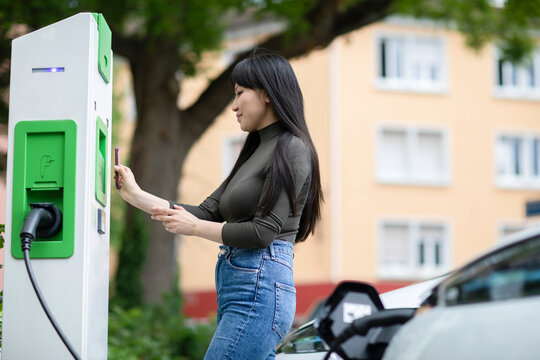 Carsharing, woman renting an electric car using smartphone
