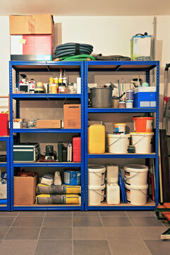 A colorful storage shelf in the basement, full packed with a lot of tools and other stuff.