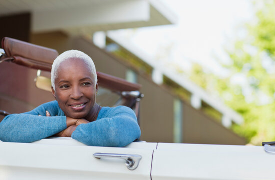 Smiling older woman sitting in convertible