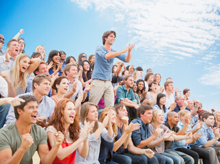 Man standing and clapping among cheering crowd