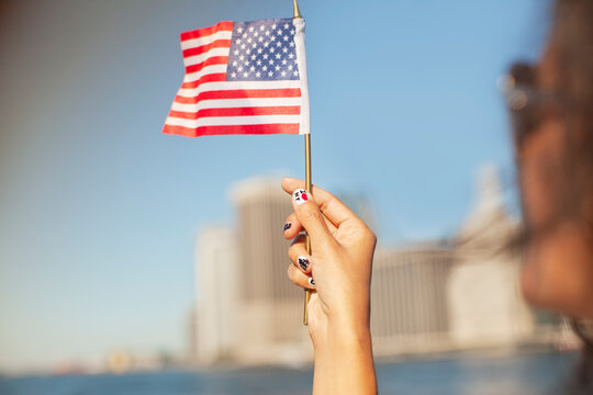 Woman with novelty nails waving American flag