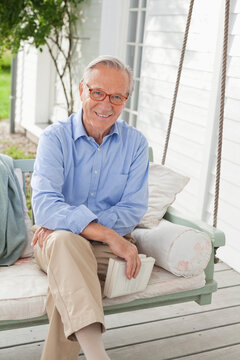 Smiling man sitting on porch swing
