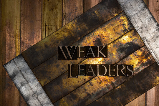 Photo of real authentic typeset letters forming text Weak Leaders on vintage textured silver grunge copper and gold background