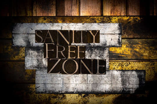 Photo of real authentic typeset letters forming text Sanity Free Zone on vintage textured silver grunge copper and gold background