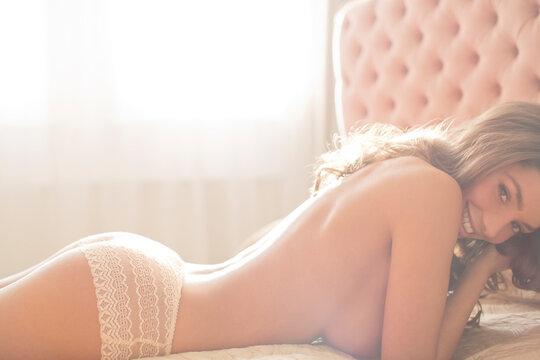 Smiling woman wearing panties on bed