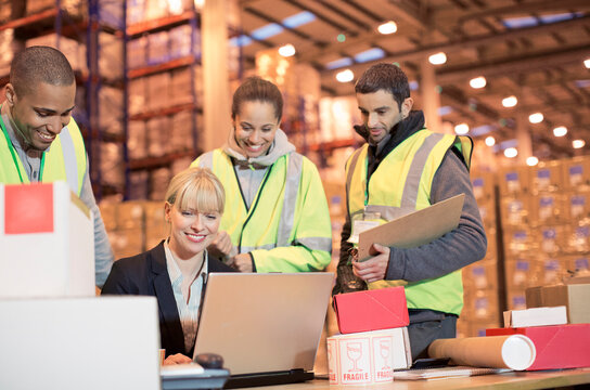 Businesswoman and workers using laptop in warehouse