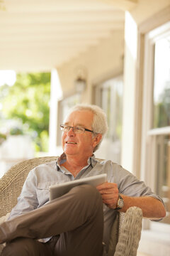 Smiling senior man using digital tablet on porch