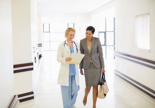 Doctor and businesswoman talking in hospital corridor
