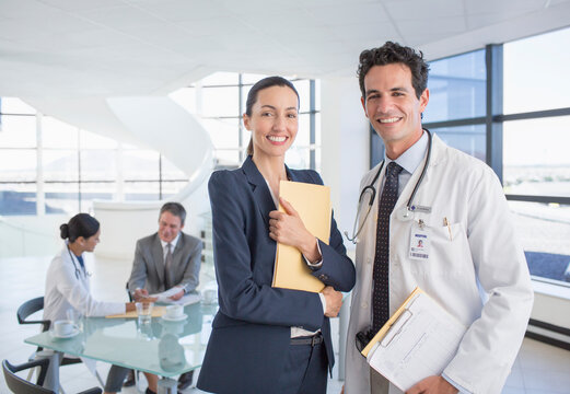 Portrait of smiling businesswoman and doctor in meeting