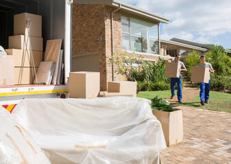 Movers carrying cardboard boxes from house to moving van