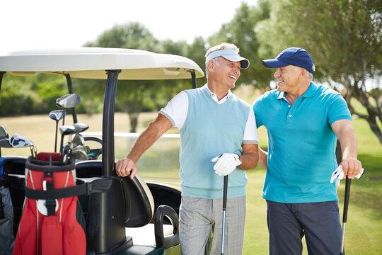 Senior men laughing next to golf cart