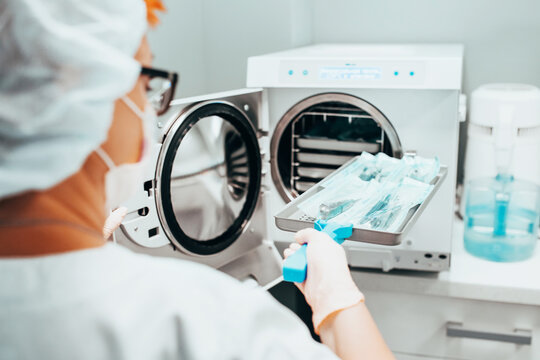 Autoclaving - Sterilization of medical instruments - a nurse loads a tray of instruments for sanitization into an autoclave