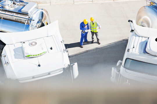 Workers reviewing paperwork near milk tankers