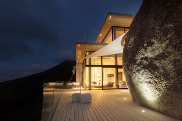 Illuminated modern house with rock feature and balcony Fotobehang