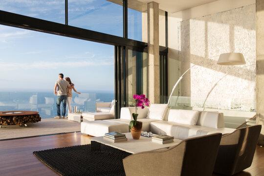 Couple standing on balcony of modern house