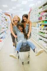 Women playing with shopping cart in grocery store