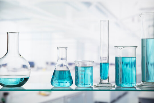 Close up of beakers with solution on shelf in lab