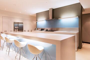 Modern white kitchen with kitchen islstools illuminated at night Wall mural
