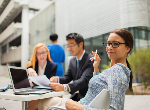 Business people talking at table outside office building