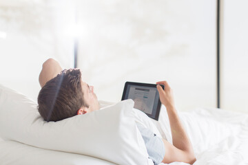 Young man lying on bed and using tablet
