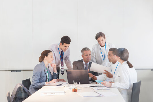 Scientists and business people talking in conference room