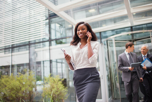Businesswoman talking on cell phone walking out of office building