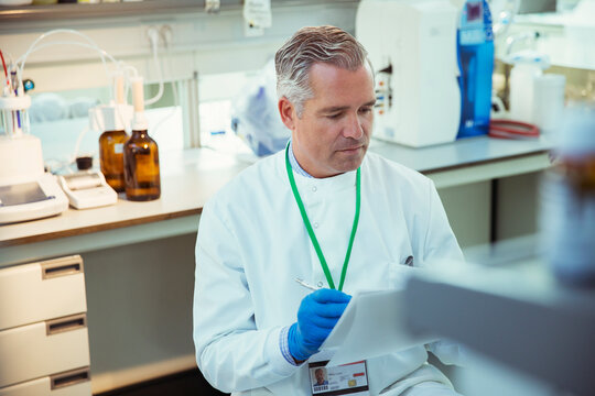 Scientist taking notes on experiment in laboratory