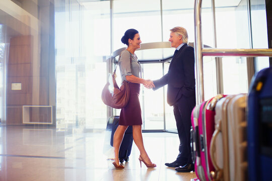 Man and woman shaking hands in hotel lobby, luggage cart in foreground